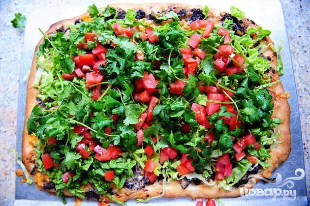 5. Убрать пиццу из духовки. Измельчить листья салата. Нарезать помидоры кубиками. Посыпать пиццу измельченными листьями салата, помидорами и листьями кинзы.