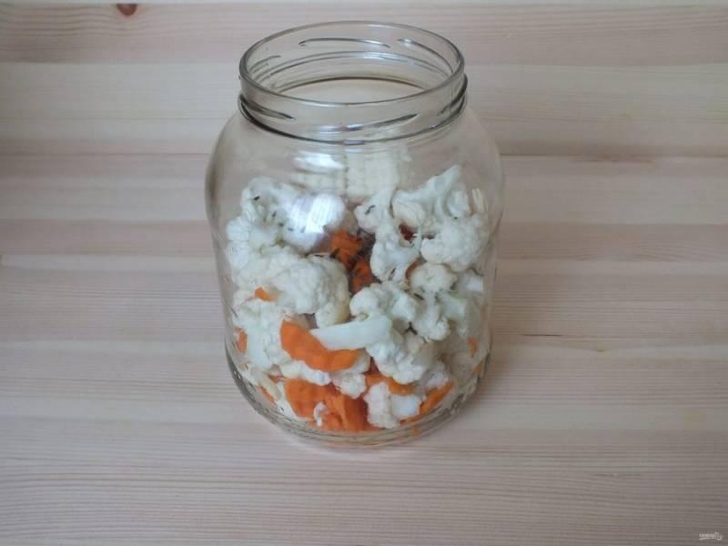 Подготовленную тару промойте с содой, обдайте кипятком. Положите слоями: капуста, морковь, чеснок, капуста и т.д. Посыпьте тмином.