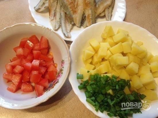 2. Очистим отваренный картофель, нарежем кубиками. Так же кубиками нарезаем помидор( по желанию, удалим сердцевину с семенами). Мелко нарежем зеленый лук или другую зелень.