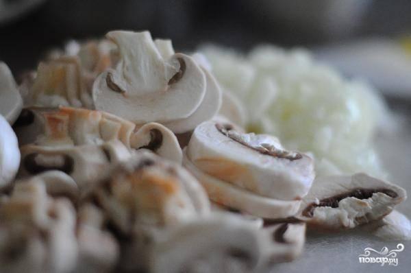 В сковороде разогреваем немного масла, пару минут обжариваем в нем мелко нарезанный лук, затем добавляем шампиньоны, солим, перчим и готовим под крышкой 5-7 минут на среднем огне.