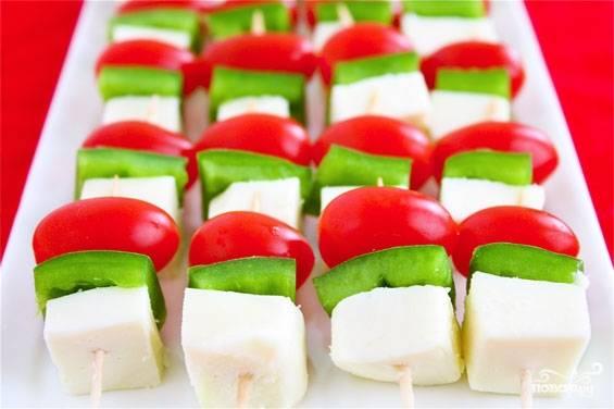 3. На шпажки или длинные кулинарные палочки наколите снизу: сыр, болгарский перец, помидор. И так до конца палочки. Выложите в сервировочную тарелку.