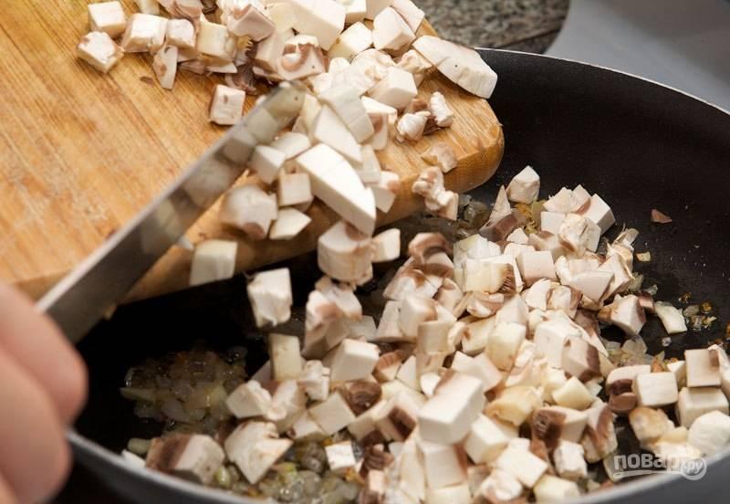 Промойте и нарежьте маленькими кубиками грибы. Добавьте их в сковороду. Перемешайте.
