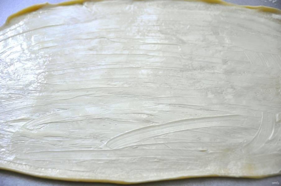 Раскатывайте каждый колобок в очень тонкий пласт, после чего смажьте  размягченным сливочным маслом.