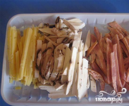 1.В первую очередь надо сказать, что в приготовлении данного салата можно использовать различные продукты, которые хранятся в вашем холодильнике. Все зависит от вашей фантазии, так как здесь можно экспериментировать.   Нарезаем тоненькими полосками сырой грибочек, твердый сыр и колбасу (грунтовые грибы сырыми употреблять не рекомендуется).
