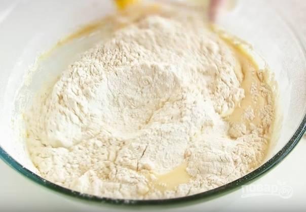 5. В тесто просейте муку, оставив часть на замес. Ложкой хорошо смешайте всё, чтобы получилось липкое тесто.