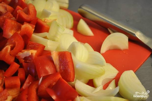 2. Лук чистим, перец очищаем от зерен. Овощи нарезаем кубиками. Добавляем к мясу. Все вместе обжариваем.