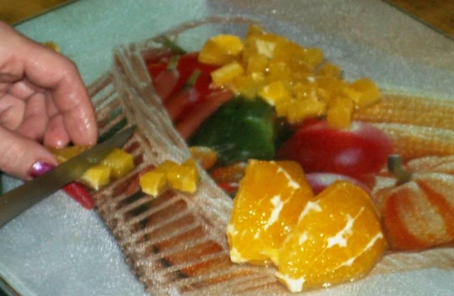 С апельсина срезаем кожуру и нарезаем его небольшими кубиками.