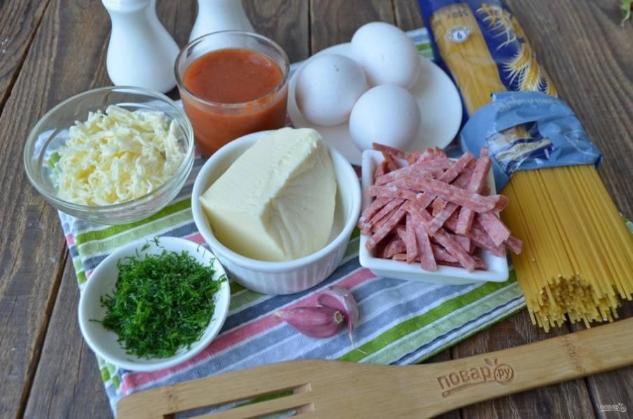 Подготовьте необходимые продукты.  Небольшую часть моцареллы или любого другого сыра (например, пармезан идеально подойдет) натрите на мелкой терке. Порежьте мелко зелень, очистите чеснок и порубите его ножом. Колбасу или бекон порежьте соломкой, так ее легче будет перемешать со спагетти. Воду для варки макарон доведите до кипения и посолите.