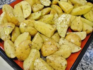 Картофель выложить на противень и поставить в разогретую до 210 градусов .духовку. Запекать около часа.