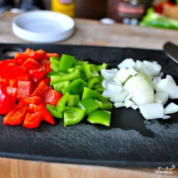 Кубиком нарезаем очищенные овощи - перцы и лук.