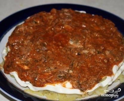 7. Подавите вилкой кильку в томате и выложите ее поверх картофеля.