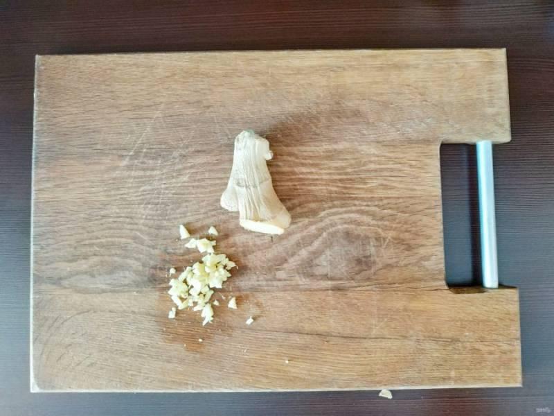 Вскипятите воду для варки пасты. Имбирь и чеснок почистите и мелко нашинкуйте.