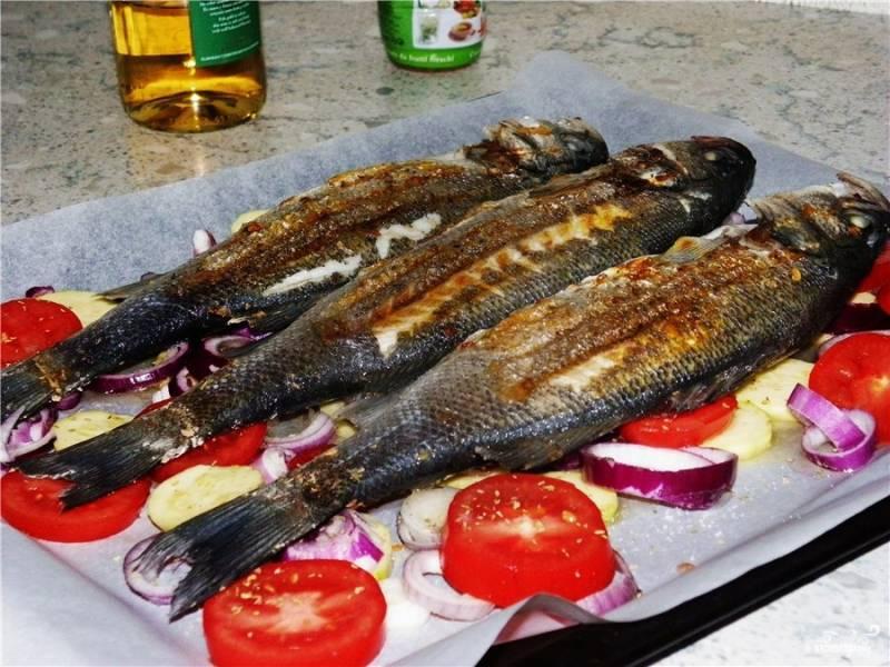 Рыбу обжарьте на раскалённой сковороде с растительным маслом по 2 минуты с каждой стороны. Это нужно, чтобы образовалась корочка. Затем выложите тушки на подложку из овощей и отправьте в духовку.