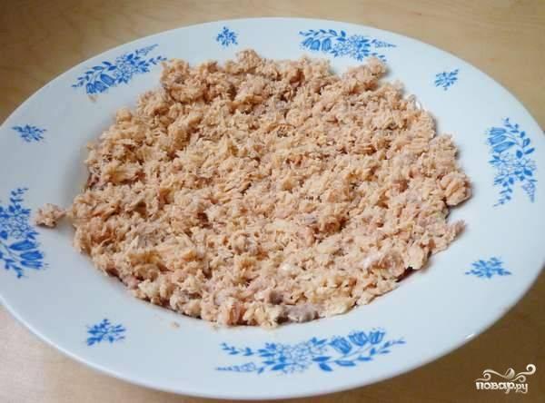 1. Первым делом нужно поставить вариться яйца и рис. Последний отвариваем в подсоленной воде. А тем временем разомните консервированную рыбку, выложите её ровным слоем на тарелку. В данном случае это горбуша, но вы можете взять и сайру, например.