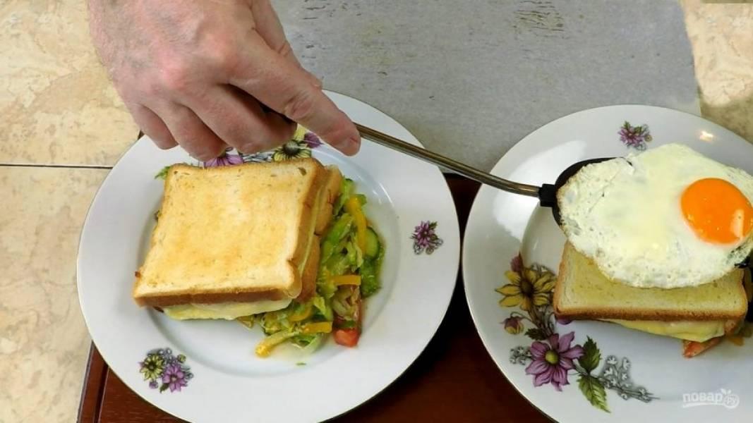 Кладём в большую тарелочку сначала салат, ставим на него сэндвич под углом, а на дамский завтрак — на хлеб, кладём глазунью.