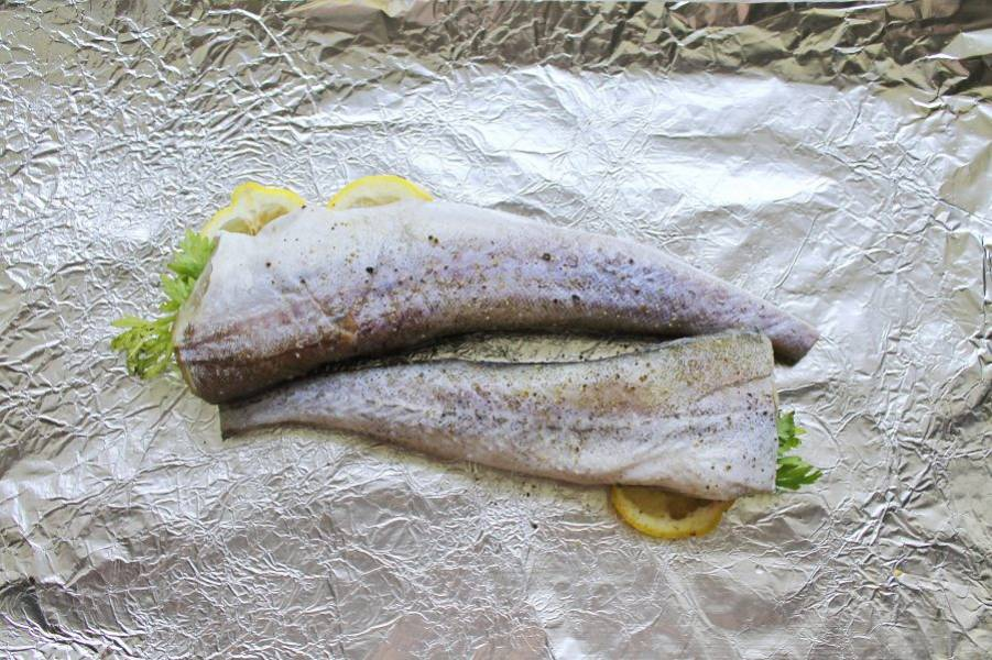 На столе расстелите фольгу для запекания и выложите на нее минтай. В брюшко каждой рыбы положите по 1-2 дольки лимона и по веточке петрушки.