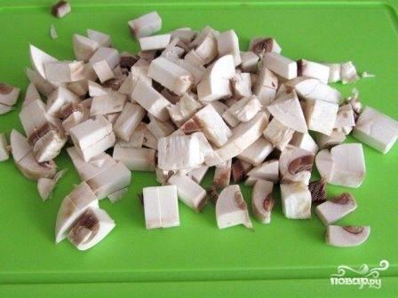 Нарежем их небольшими кубиками. В принципе, размер нарезки грибов вы можете регулировать самостоятельно, ориентируясь на собственные предпочтения.