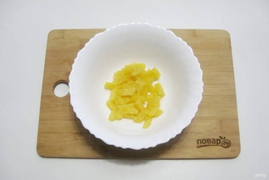Ананас нарежьте небольшими кубиками и выложите в салатник.