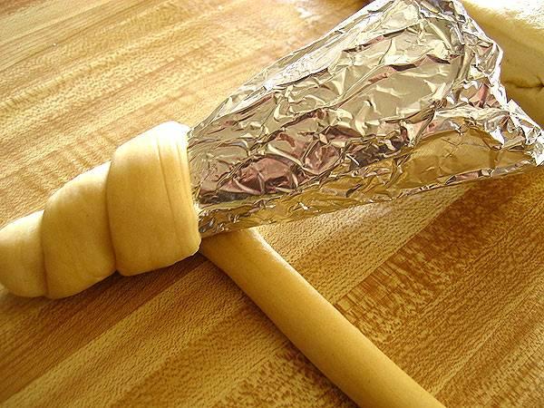 1. Чтобы все сделать правильно, используйте конус из бумаги или картона. Обматаем его фольгой, а затем - подготовленным тестом по кругу. Пока тесто мягкое, посыпьте его солью и специями, если хотите.
