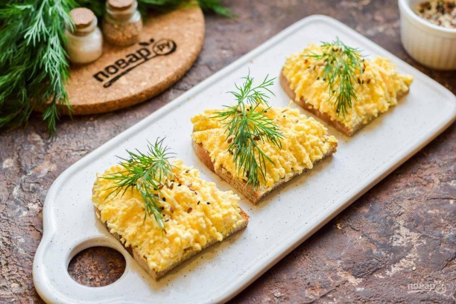 Выложите смесь яиц и сыра на кусочки хлеба, украсьте семенами кунжута. По желанию добавьте по веточке укропа. Подавайте бутерброды к столу.