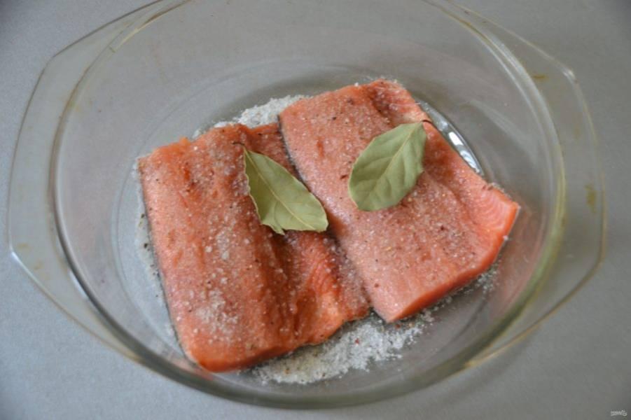 Выложите рыбу кожей вниз, посыпьте посолочной смесью, добавьте лавровый лист.