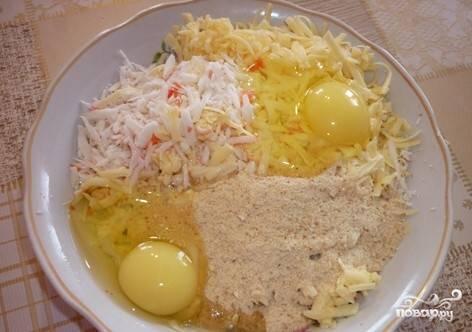 4.Тертый сыр, крабовые палочки и чеснок выкладываем в посуду, вбиваем туда 2 яйца и добавляем муку и сметану. Солим, перчим. Можно также добавить другие специи на свое усмотрение. Тщательно все перемешиваем до получения однородной массы.