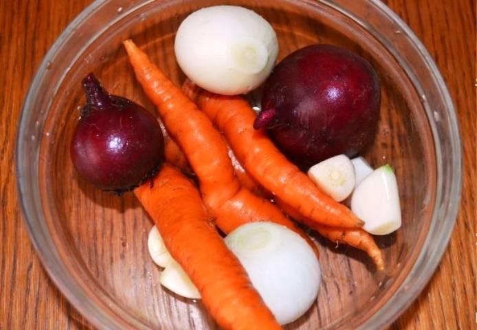 Очистите лук и чеснок, вымойте свеклу и морковь. Все овощи порежьте крупными кусками на 3-4 части.