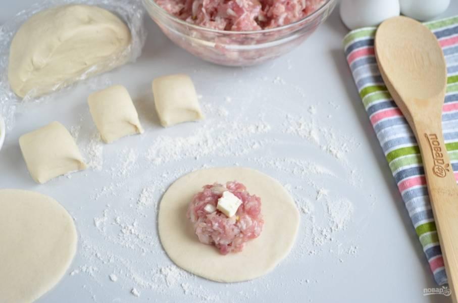 Разделите тесто на 4 части. Из каждой скатайте жгутик диаметром 4 см, который разрежьте на кусочки (примерно по 3 см). Каждый кусочек раскатайте тонко, диаметр — 9 см. Положите в центр каждой лепешечки полную столовую ложку фарша и кусочек масла.