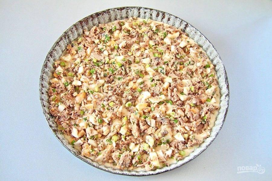 Форму для выпечки смажьте растительным маслом и присыпьте бока и дно мукой или манкой. Равномерно распределите примерно половину порции теста. Сверху положите начинку.