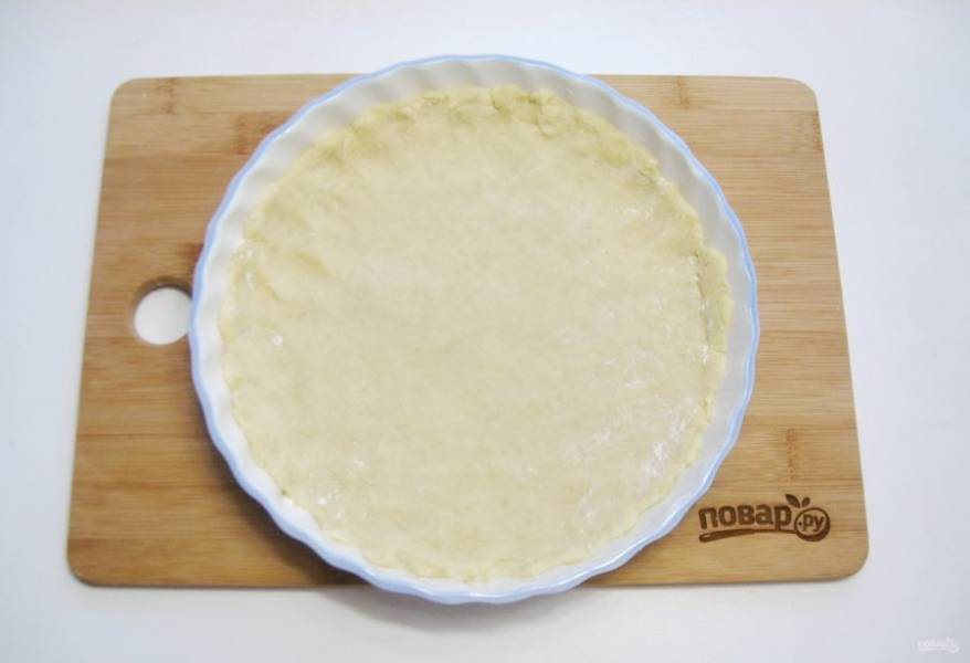 Достаньте тесто из холодильника, разделите на две части. Одну выложите в форму для выпечки.