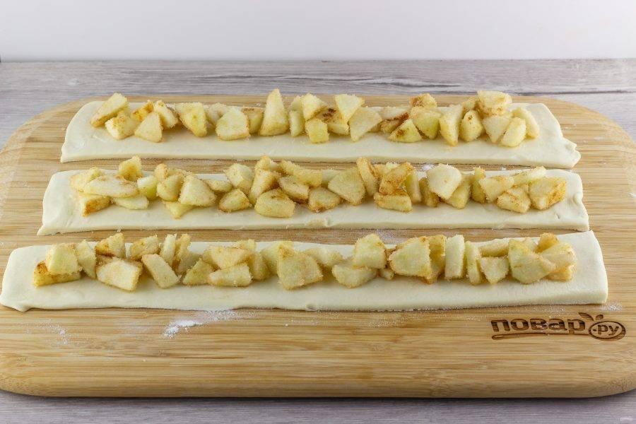 Яблоки помойте, очистите от сердцевины и кожуры. Мелко порежьте, смешайте с сахаром и корицей. Выложите на полоски теста так, чтобы остались бортики для защипов.