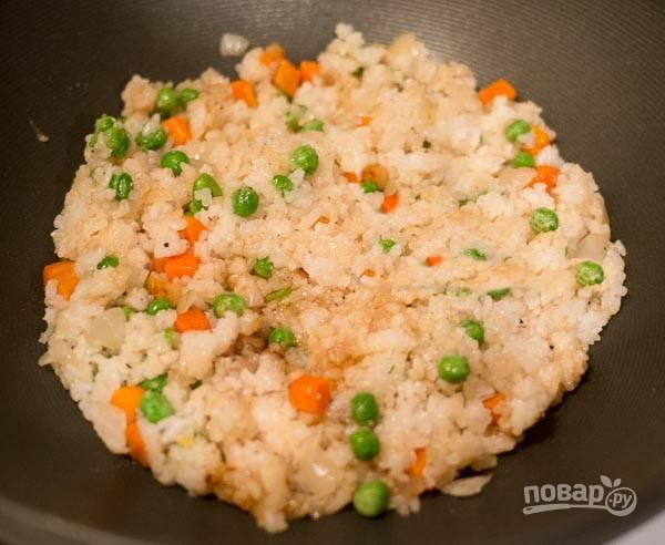 6. Добавьте соевый соус, рис в сковороду, залейте бульоном. Пропарьте рис под крышкой 20 минут.