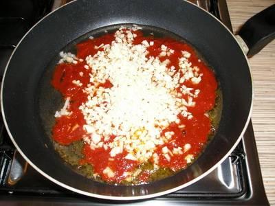 Разогреваем на сковороде масло и слегка обжариваем томатную пасту с чесноком.