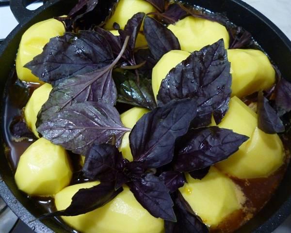Чистим картофель и кладем его в казан, также добавляем листья базилика. Картофель солим по вкусу. Томим блюдо на очень медленном огне под крышкой, примерно 1 час.