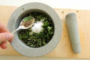 Травы и чеснок поместите в ступку, добавьте соль и перец.
