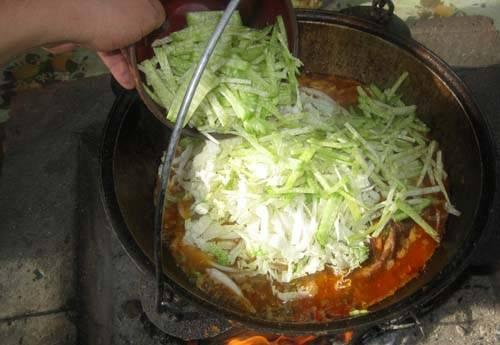 Добавьте капусту и редьку, жидкость должна покрывать овощи не более, чем на 1 см.
