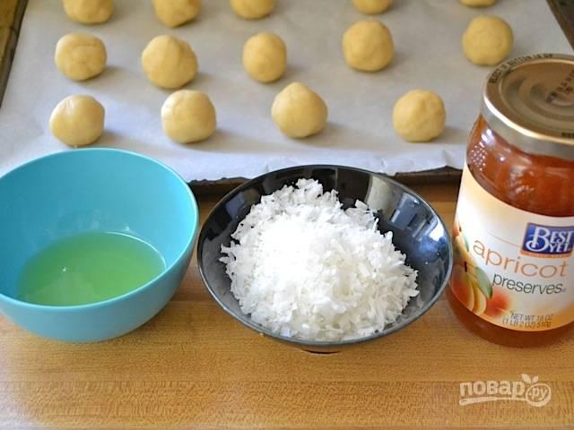 8.Выложите шарики на противень с пергаментом. Подготовьте миску с белком, в другую выложите кокосовую стружку.