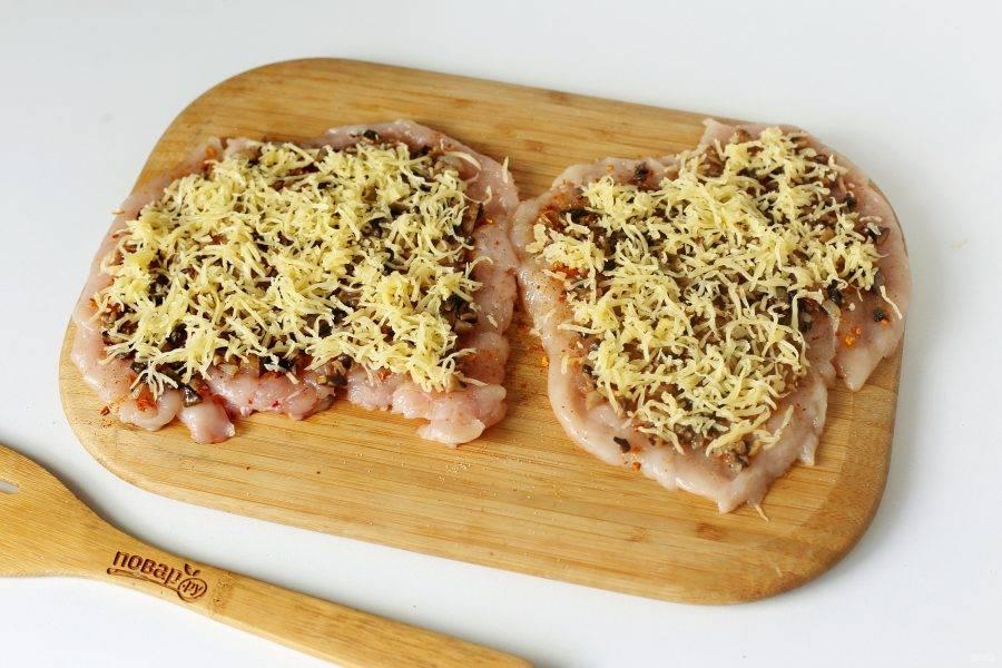 На отбитое мясо выложите грибную начинку, а затем посыпьте ее тертым сыром.