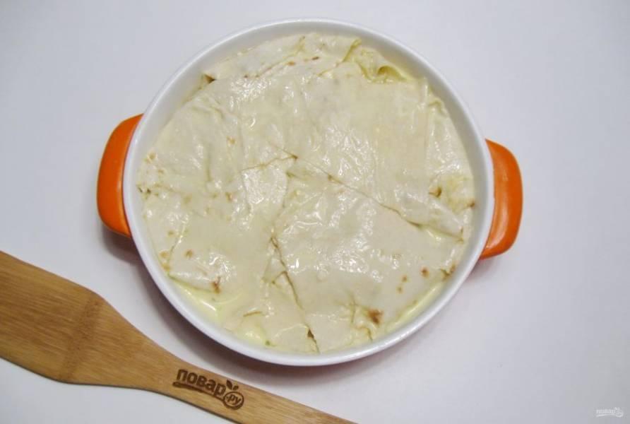 Затем выложите следующий лист лаваша и смажьте растопленным сливочным маслом. После следующий лист смочите в заливке и посыпьте сыром. Так поступайте, пока не заполните всю форму. Накройте сабурани свисающими краями лаваша. Проткните в нескольких местах пирог ножом и залейте оставшейся смесью молока и яиц.