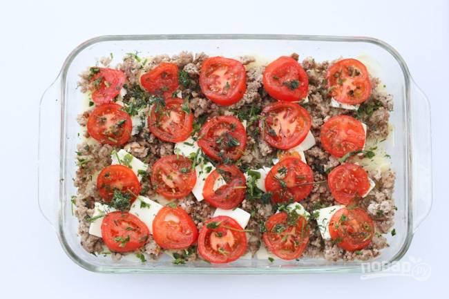 5.Вымойте помидоры и тонко нарежьте кружочками, затем выложите их в форму, добавьте мелко нарубленную зелень и специи.