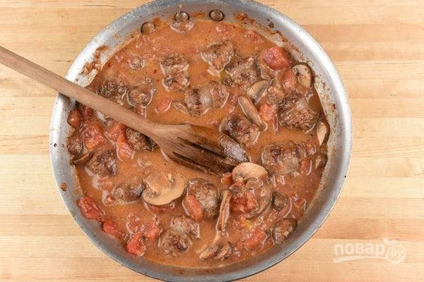 5. Затем в глубокую сковороду добавьте нарезанные помидоры, сосиски, натрите моцареллу и всыпьте соль и перец. Доведите всё до кипения и тушите 5 минут.