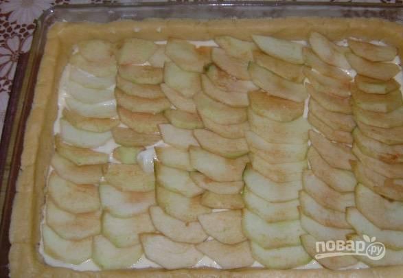 6. Тесто раскатайте тонким пластом и выложите в жаропрочную форму. Сверху распределите творожную начинку и яблоки. Отправьте пирог в разогретую до 180 градусов духовку примерно на полчаса.