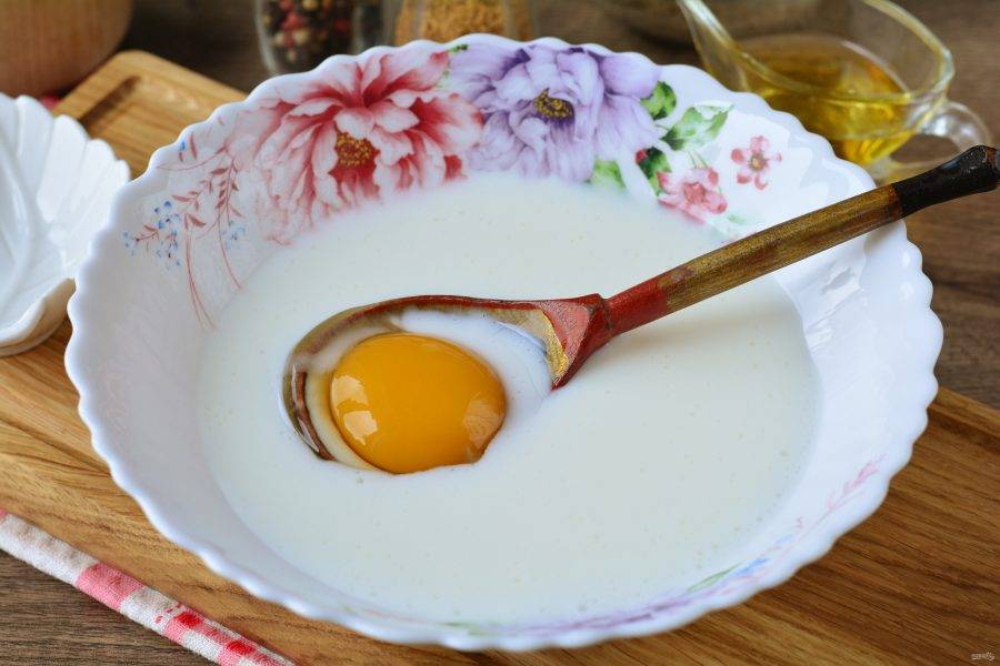 Вбейте в тесто куриное яйцо и хорошо перемешайте.