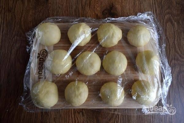 6. Подошедшее тесто разделите на 20 равных частей, округлите и накройте пищевой пленкой.