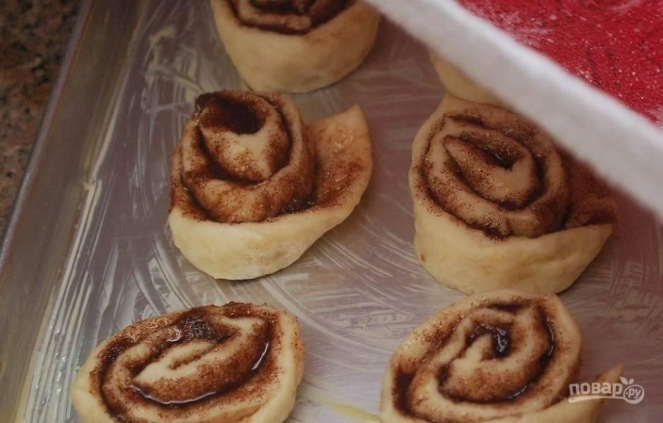 Нарежьте получившийся рулет на небольшие кусочки (4 см в ширину) и уложите на смазанный маслом противень. Накройте булочки полотенцем и дайте подойти 15-20 минут.