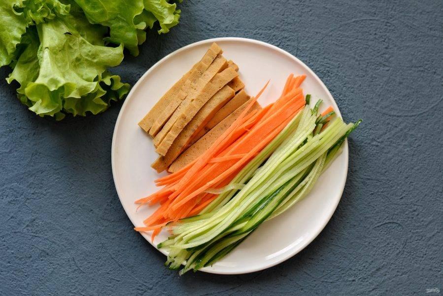 Нарежьте брусочками пшеничную колбасу, морковь и огурец натрите на корейской терке. Салатные листья разделите, сверните рулончиком.