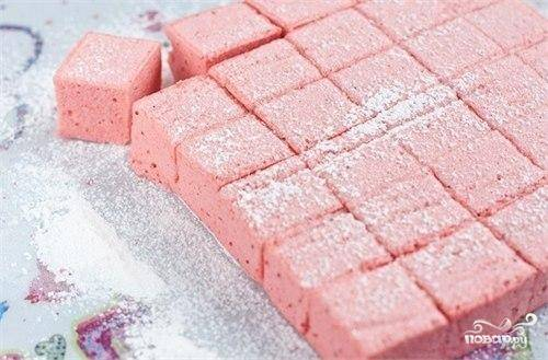 Застывший клубничный рахат-лукум достаем из формочки, посыпаем сахарной пудрой, нарезаем на кубики и подаем.