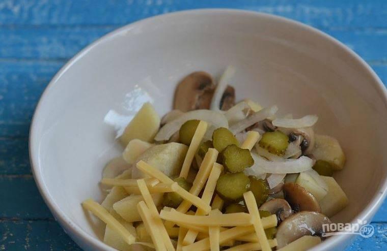 Выложите обжаренные грибы и отварной картофель в миску, добавьте к нему нарезанный репчатый лук, корнишоны и твердый сыр. Посолите и поперчите салат.