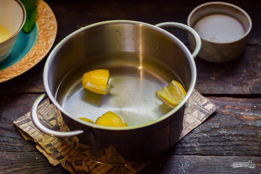 В кастрюлю влейте воду и выложите выдавленные дольки лимона.