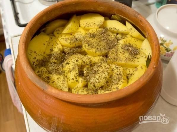 Добавьте в горшочек к мясу толченые кедровые орешки. Затем очистите картофель, вымойте его и нарежьте на кружочки. Выложите картофель поверх мяса с овощами, посолите, поперчите и добавьте сушеный базилик.
